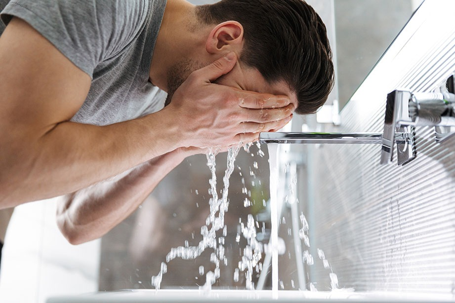 Photo of young man indoors washing his face.