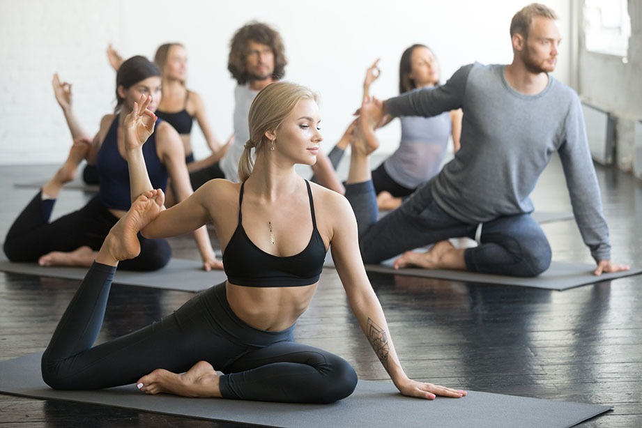 Group of young sporty people practicing yoga lesson with instructor, sitting in Mermaid exercise, Eka Pada Rajakapotasana pose, working out, indoor full length, students training in club, studio